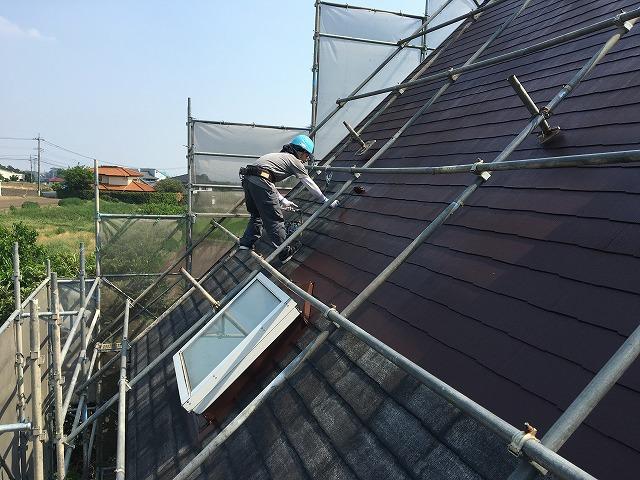 天窓ついている住宅の屋根で作業を行っている職人