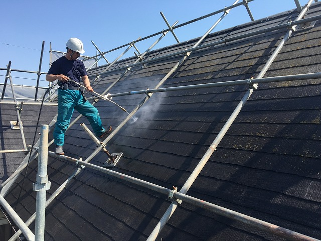 高圧洗浄をし、屋根の汚れを落としている作業員