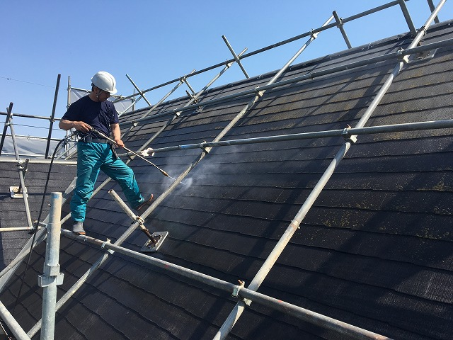 屋根を高圧洗浄している作業員
