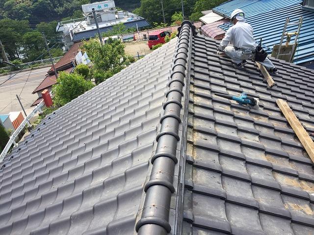 瓦屋根の上で作業をする瓦職人さん