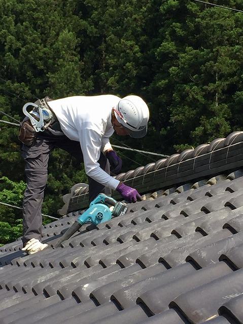 工具を使って瓦に付いた汚れを落としている作業員
