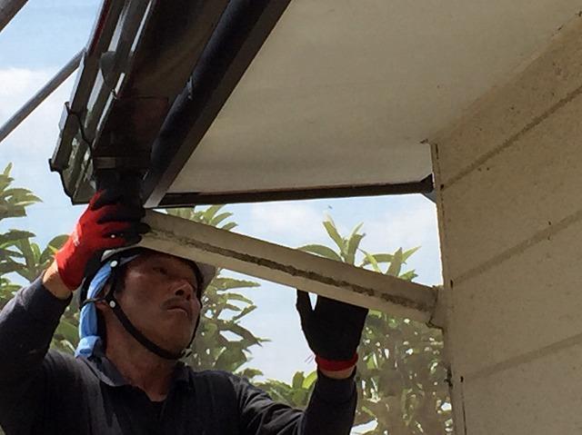 筒状の雨樋のパーツを付けている職人