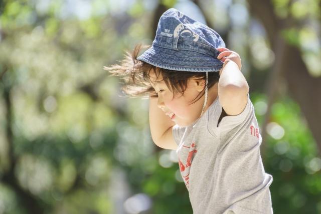 強い風で帽子を飛ばされそうになる子供