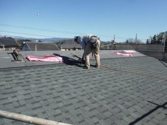 もう片方の屋根にも屋根材を専用のくぎ打ち機を使い貼っていく職人さんの写真