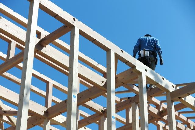 建築中のお家の骨組みの上に立つ職人