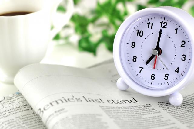 新聞の上に置かれた時計