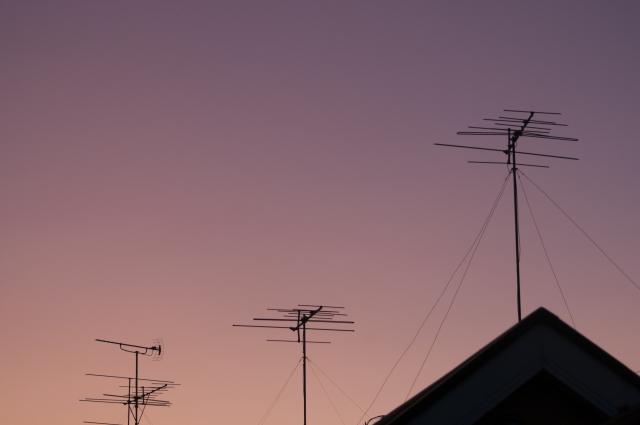 夕暮れ時の屋根上のアンテナ