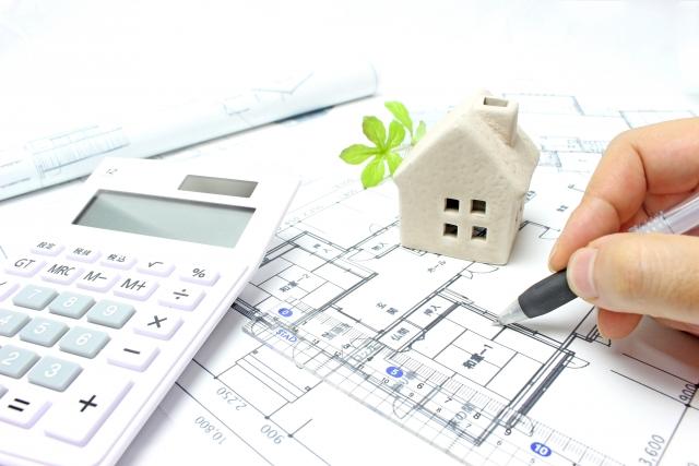 設計図・住居の模型・電卓が置かれたデスクの上