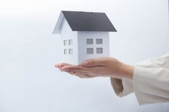 手の平に乗せた家の模型