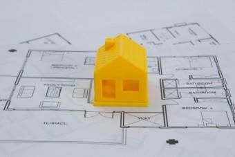 設計図の上に置かれた黄色い三角屋根の家の模型