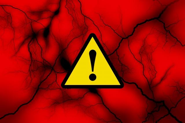 赤い背景に浮かぶ危険マーク