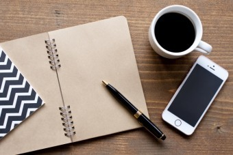 テーブルの上に置かれたコーヒー・手帳・ペン
