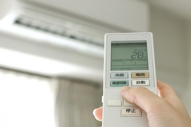 エアコンにリモコンをかざす人