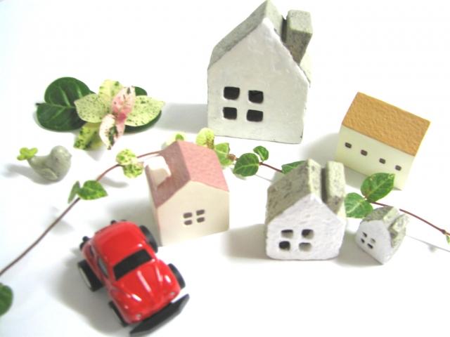 用紙の上の置かれたお家の模型と車の模型