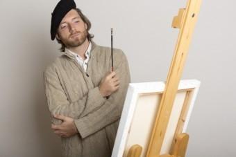 白いキャンパスの前で考え込む絵師