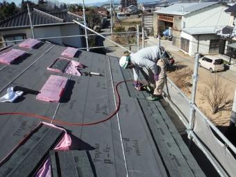 屋根材を専用のくぎ打ち機を使用し止めている作業風景