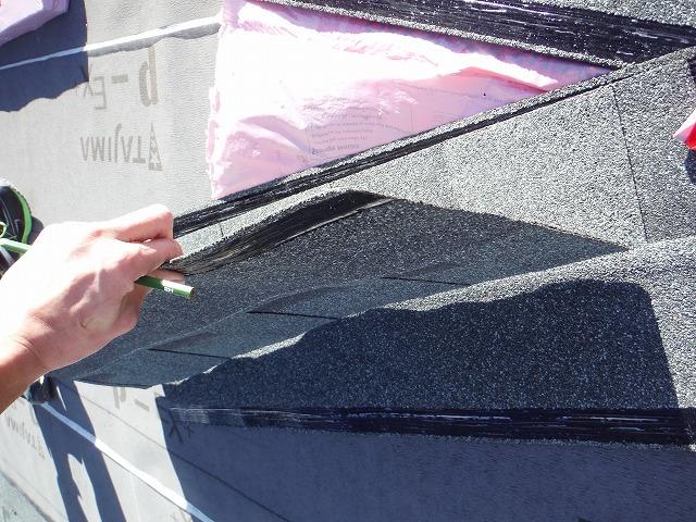 これから張る屋根材の裏に接着剤(黒色)を下準備として塗っている写真