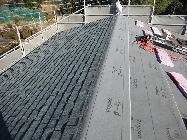 屋根材貼り付け作業の途中経過で、片側だけ屋根材が貼り終わった写真