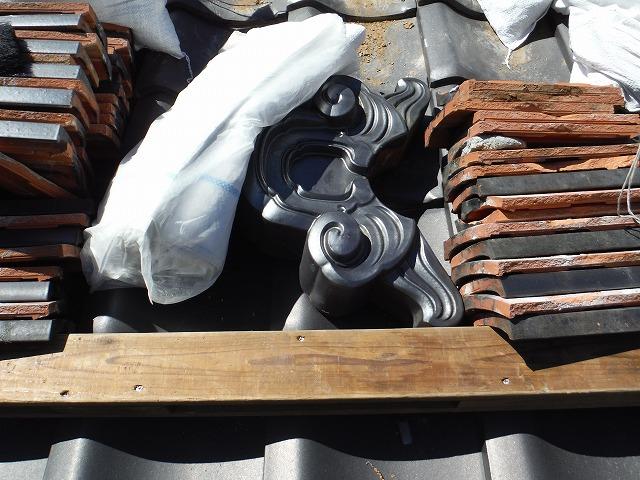 落下防止の板の上に置かれた瓦や袋