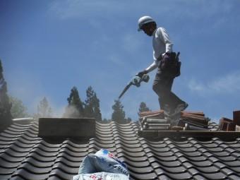 空気の出る機械(ブロワ―)で屋根の埃を飛ばしている作業員