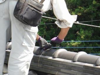 銅線を使って重なった瓦を固定している作業員