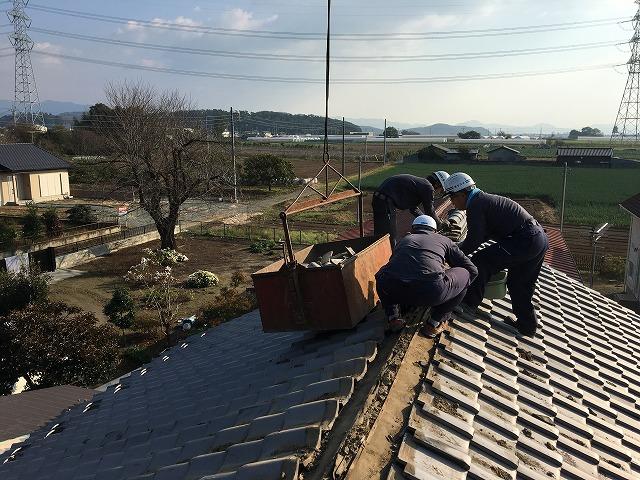 瓦屋根を葺き替えている作業員