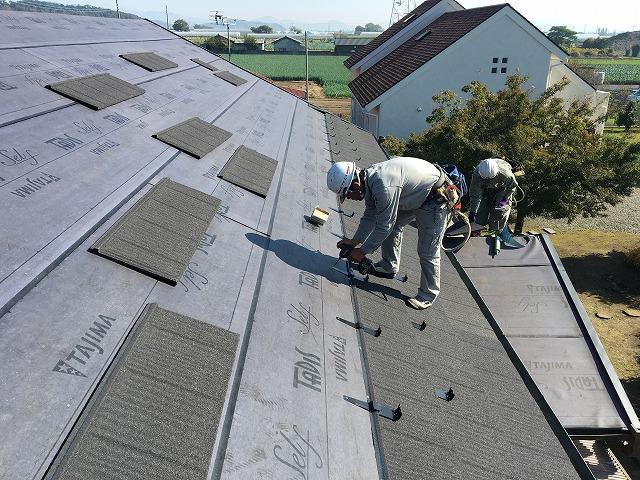 屋根材を張っている職人