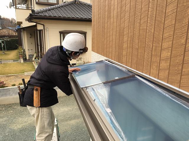 屋根材をはめている作業風景