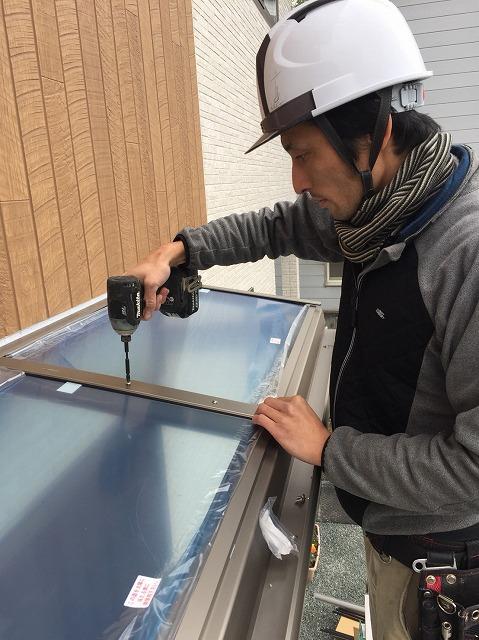 屋根材を入れ、ビスで固定をする作業