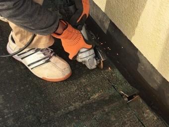 排水溝近くのベランダ床を切断している作業員