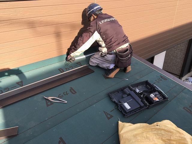 張られているルーフィングシートの余分な所を切り落としている職人
