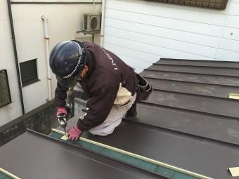 板金屋根材を屋根面に取り付けている職人