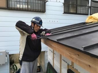 板金屋根の軒部分を加工している職人