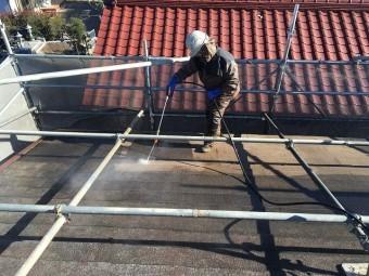 高圧洗浄機を使い、屋根の洗浄を行っている作業員