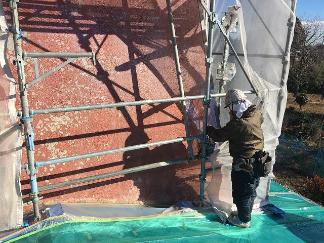 屋根面の足場にネットを張っている作業員