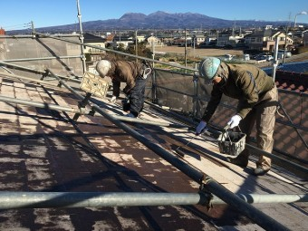 屋根の裏側で下地塗料のシーラー剤を塗っている作業員