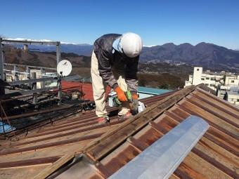 屋根の上で部材の加工をしている屋根屋