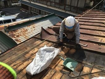 金属屋根の解体工事で古い防水紙を剥がす屋根屋さん