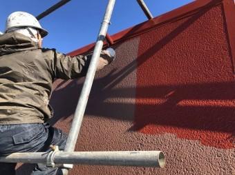 正面の屋根面を塗装している作業員