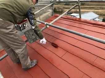 裏側の屋根面を塗装している作業員
