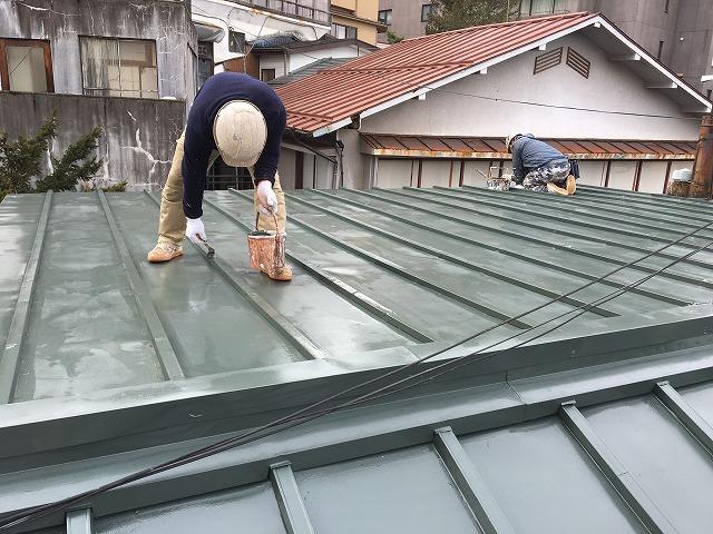 板金屋根に濃い緑色の塗装を施している作業員