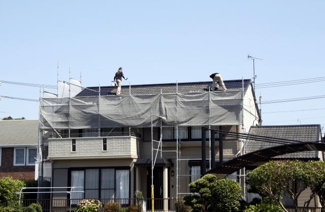 屋根の上で作業している塗装屋さん
