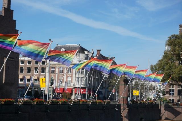 虹色の旗が水路に立てられたオランダの街並み
